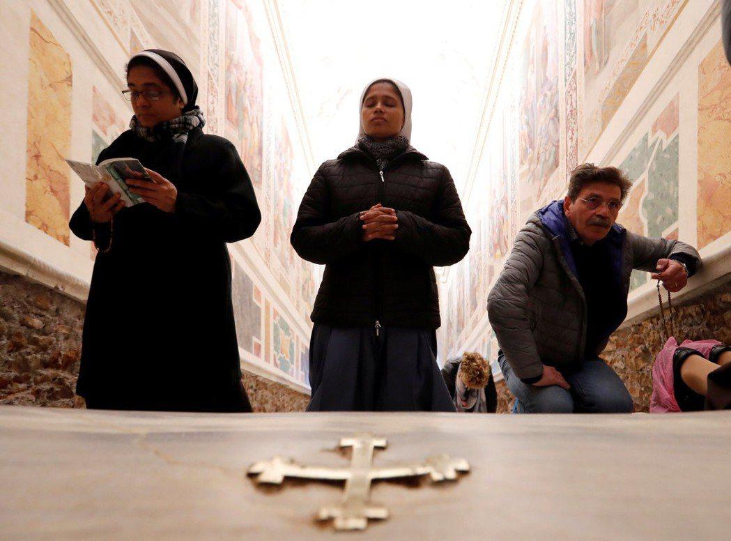 相傳耶穌曾在階梯上三處滴下「寶血」,這些點也被以中世紀十字架做記號,參訪信徒跪著...