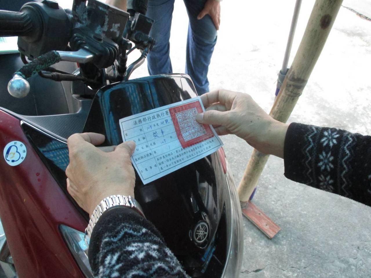 執行署人員在機車貼上封條。記者余衡/翻攝