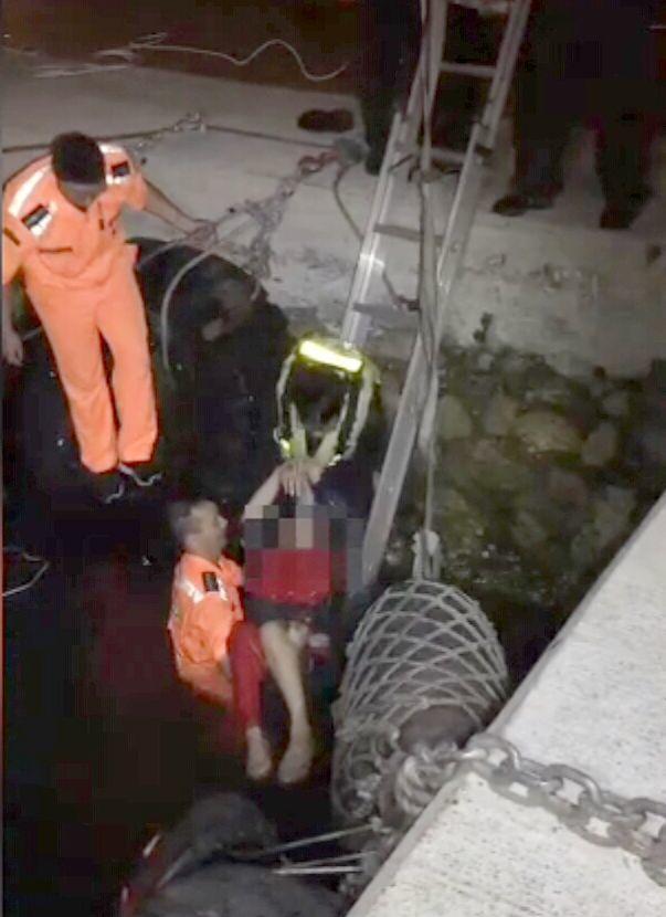 劉姓女子因岸邊沒護欄,不慎落海,海巡人員正搶救她上岸。記者林保光/翻攝