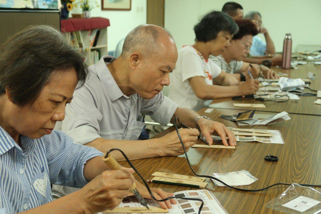 長輩參加「非做BOOK--隨心烙畫木書籤」活動,仔細完成作品。記者徐如宜/攝影