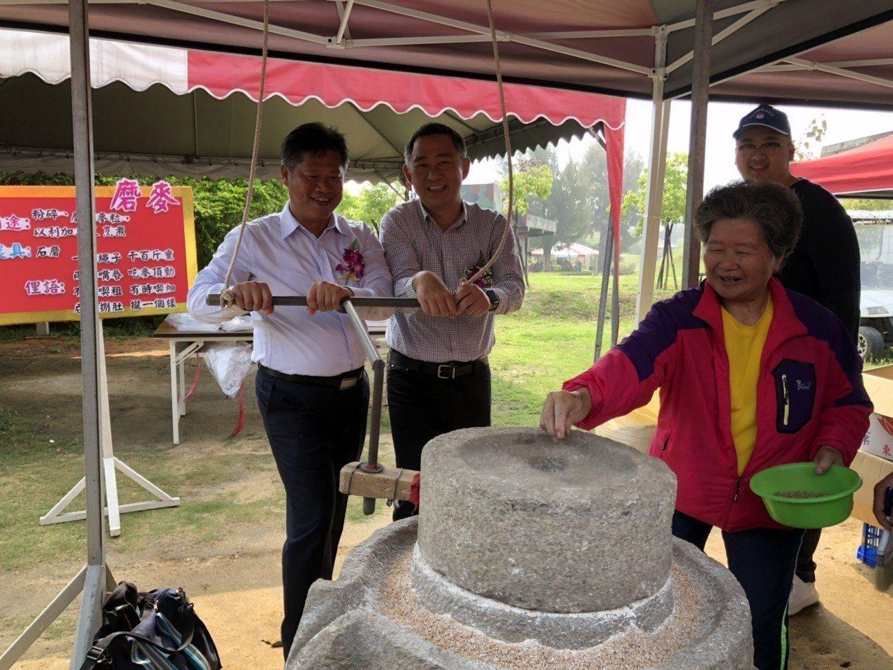 金門縣長楊鎮浯(左二)和金寧鄉長楊忠俊(左一)一起體驗傳統的磨麥,兩人攜手推著石...