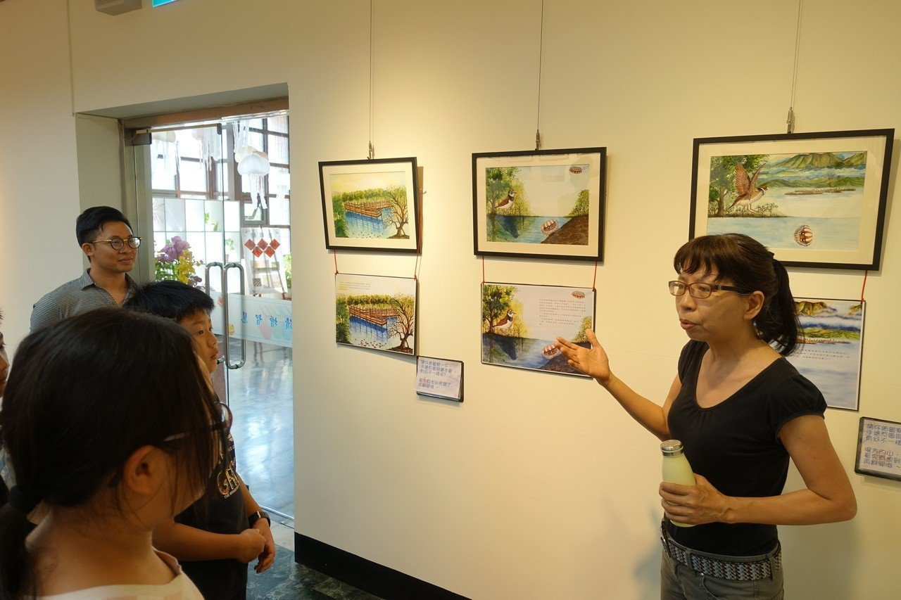 高市林園區第一本生態繪本「倒立水母小非找朋友」繪本文字創作者者蘇曼麗(右)跟學童...
