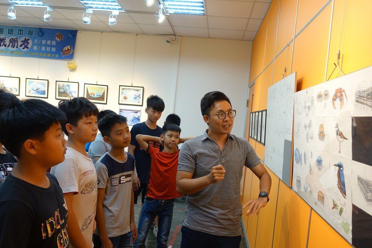 高市林園區第一本生態繪本「倒立水母小非找朋友」繪本繪圖者葉哲翰(右)跟學童們導覽...