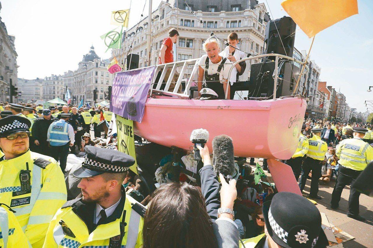 環保團體十九日在倫敦牛津街圓環示威,艾瑪湯普遜站在小船上回答記者問題。 (法新社...