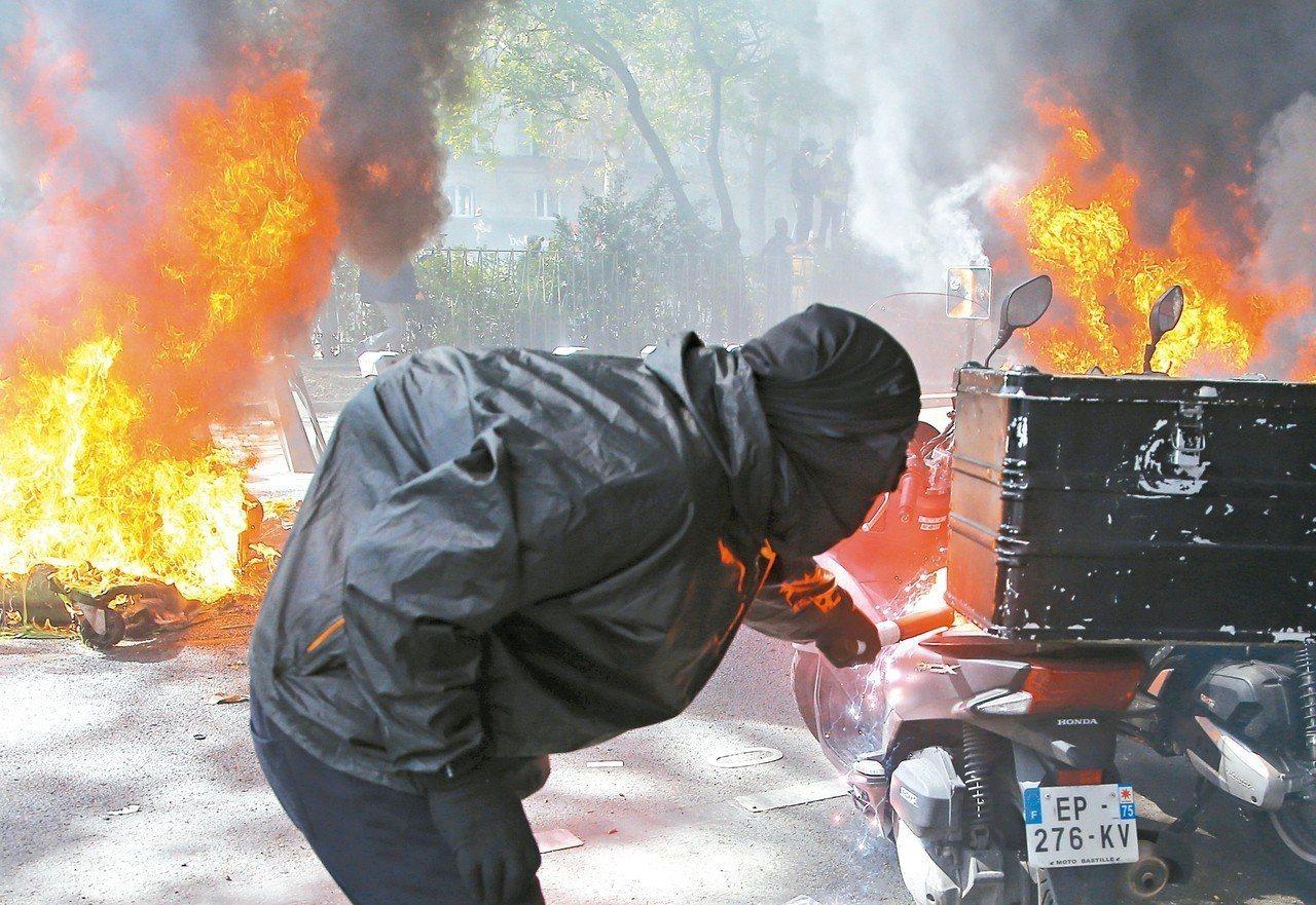 法國「黃背心」運動20日再上街抗議,一名抗議分子在巴黎街頭點燃一輛機車。 美聯社