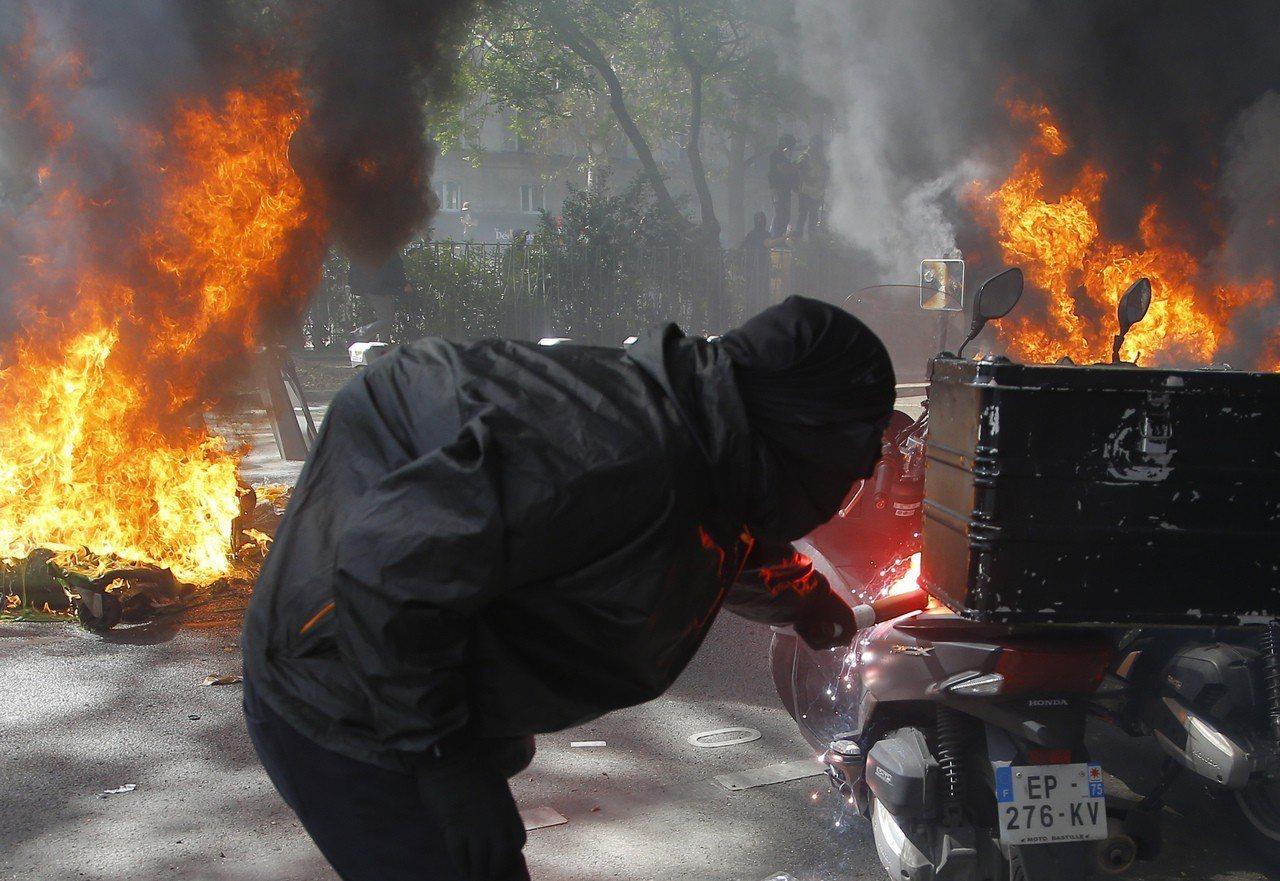 法國「黃背心」運動20日再上街抗議,一名抗議分子在巴黎街頭點燃一輛機車。美聯社