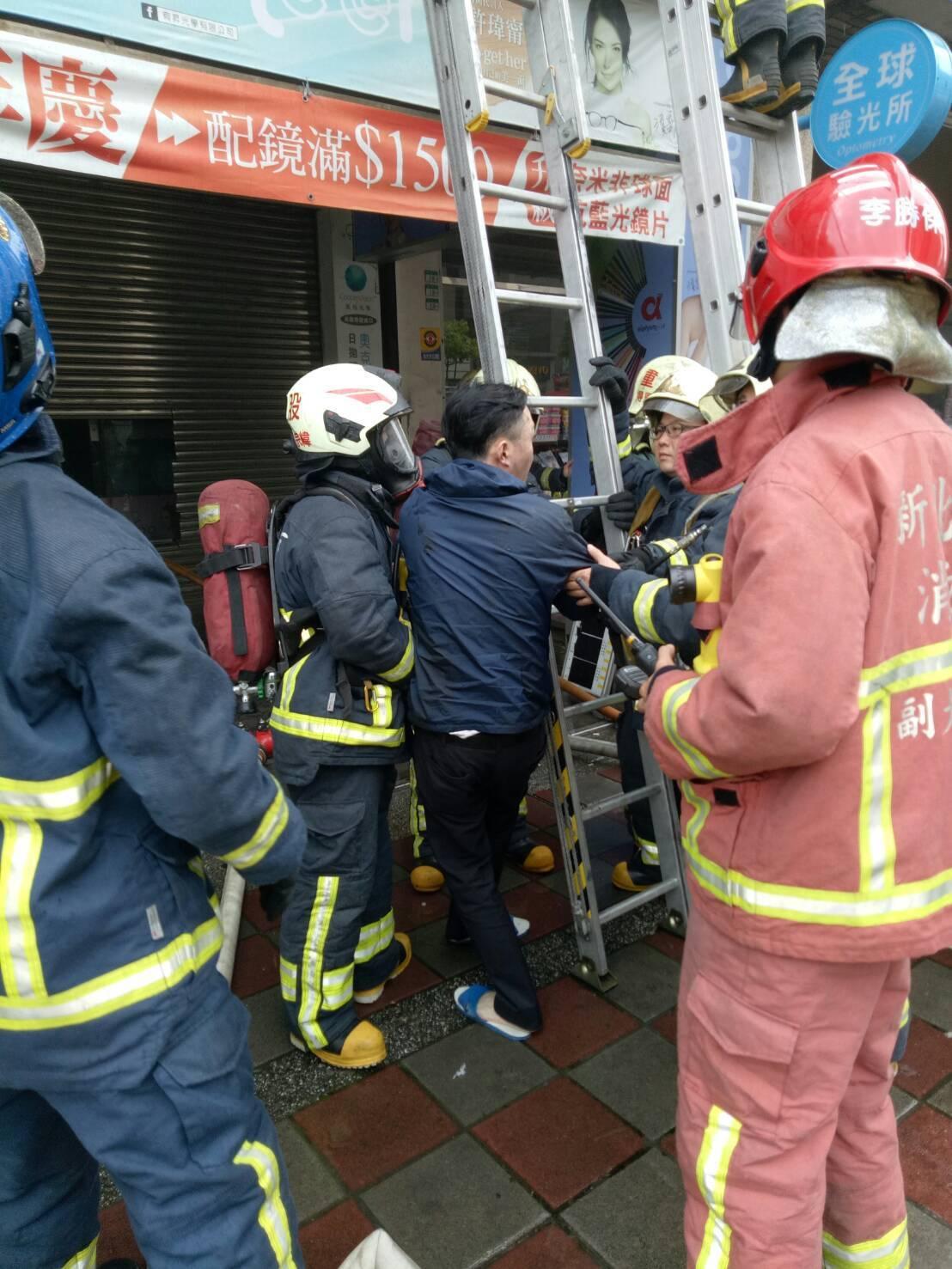 消防隊員割開外牆廣告布幔救援受困住戶。記者林昭彰/翻攝