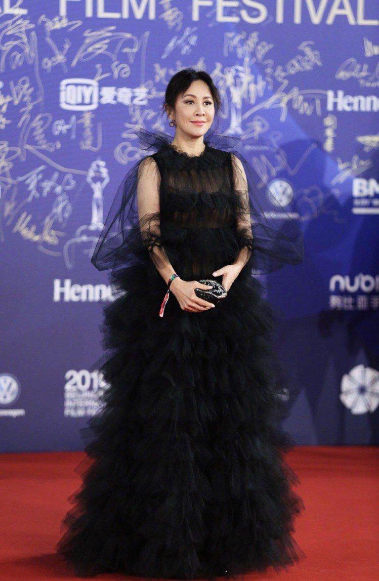 劉嘉玲在閉幕式上穿了愛牌Valentino的早秋系列黑色薄紗禮服,大蓬袖與層層堆...