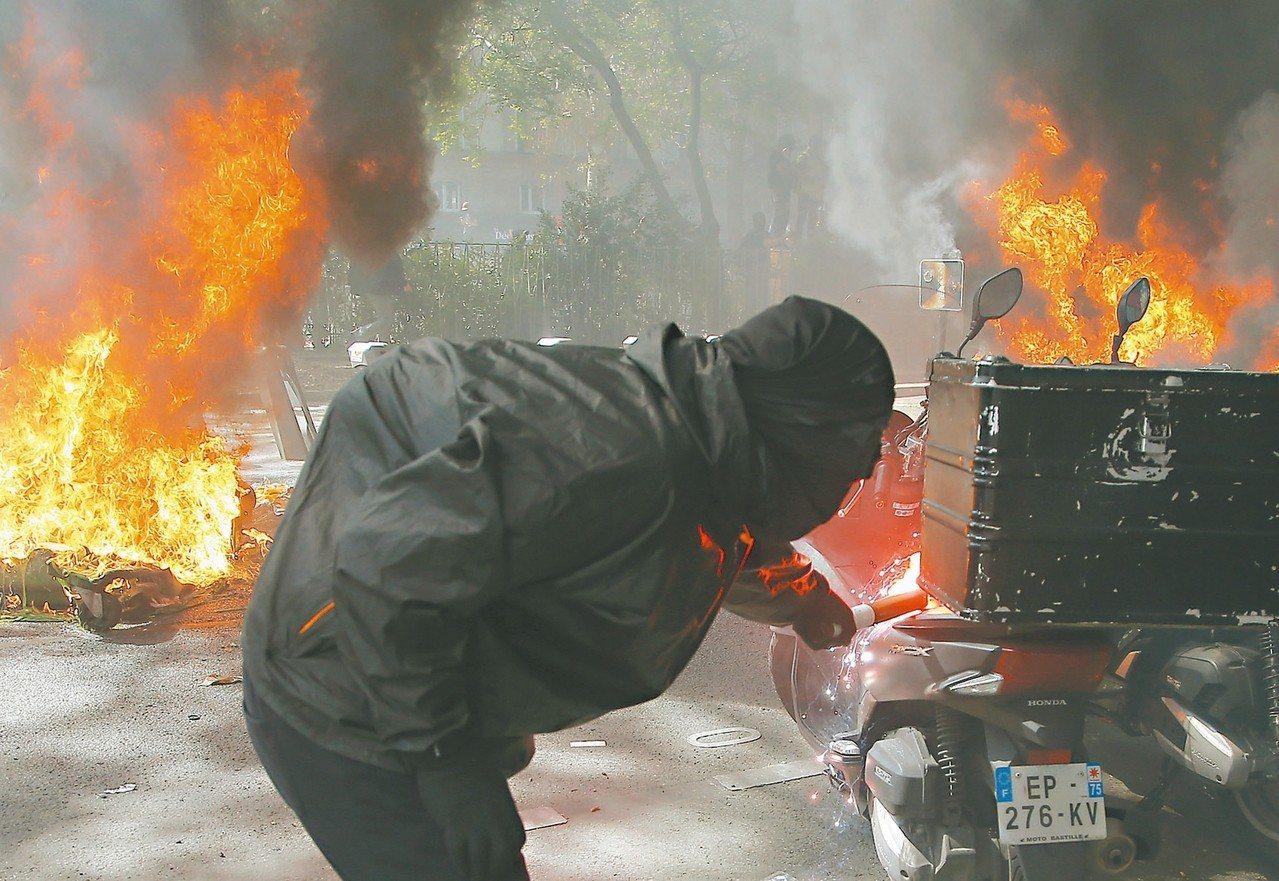 法國「黃背心」運動廿日再上街,一名抗議分子在巴黎街頭點燃一輛機車。 (美聯社)