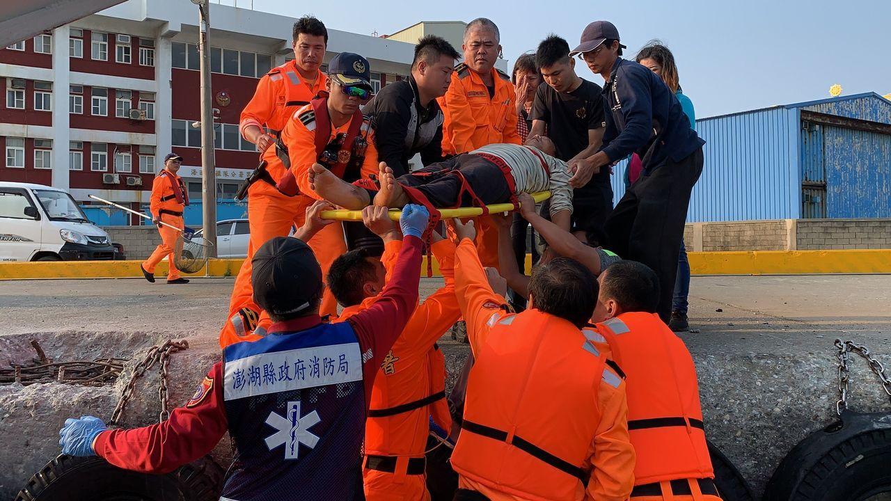 澎湖海巡隊今天將昏迷的漁船船長救上岸,家屬聞訊在港邊不禁掩臉哭泣。記者林保光/翻...