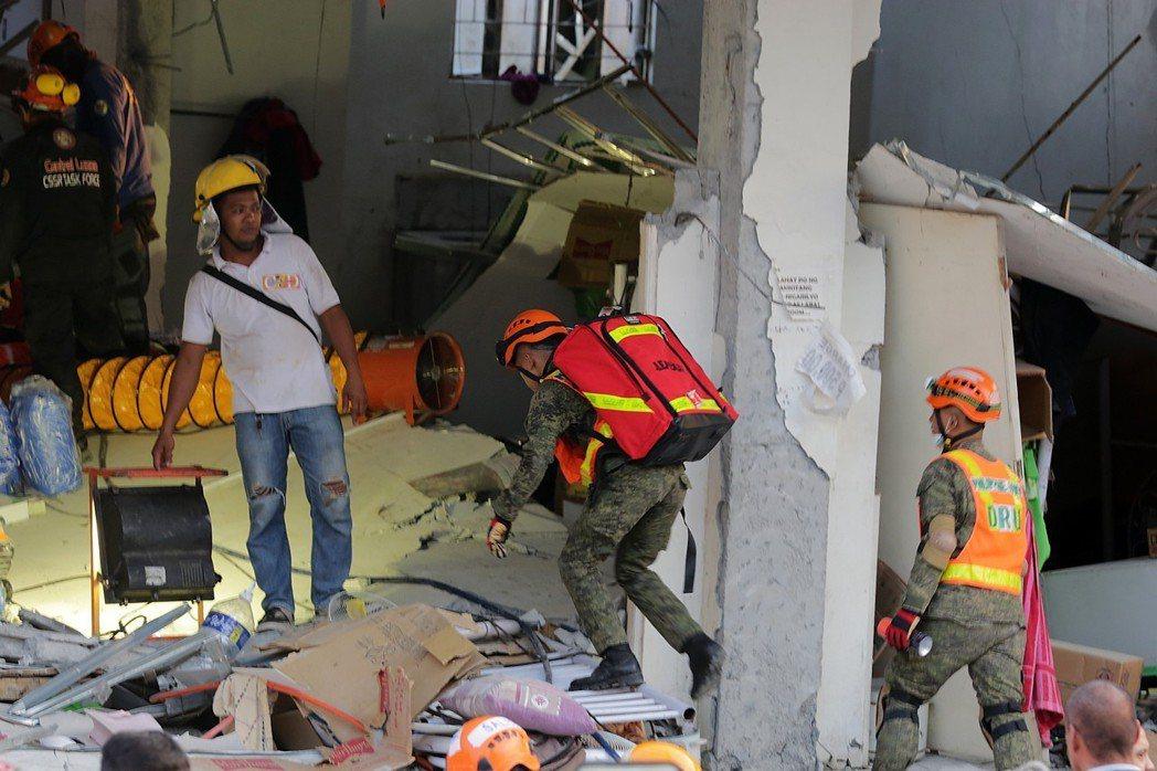 救難人員23日在倒塌的建築物內搜救。新華社