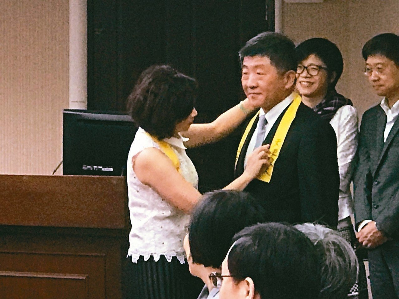 立委陳靜敏(左)為衛福部長陳時中(中)繫上黃絲帶,表達聲援護理師。 記者簡浩正/...