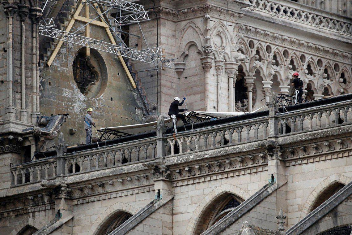 圖為修復工人正在聖母院進行防雨設置作業。 圖/路透社