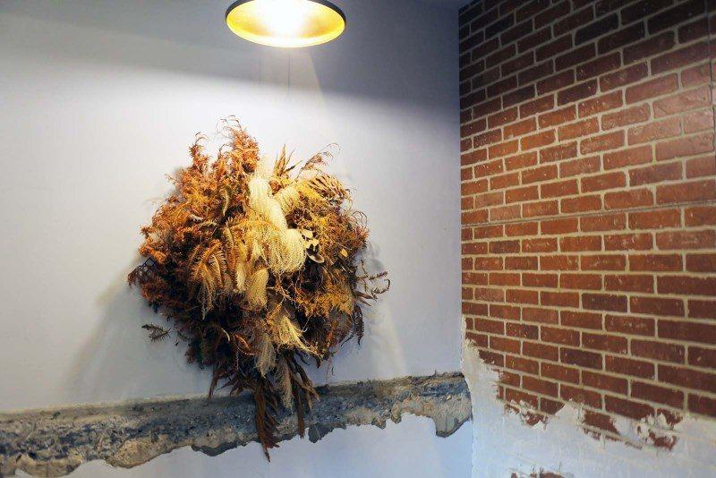 (圖/台灣旅行趣) ▲樓梯轉角處有一個超大乾燥花,燈光照射至紅磚與清水模牆上,截...