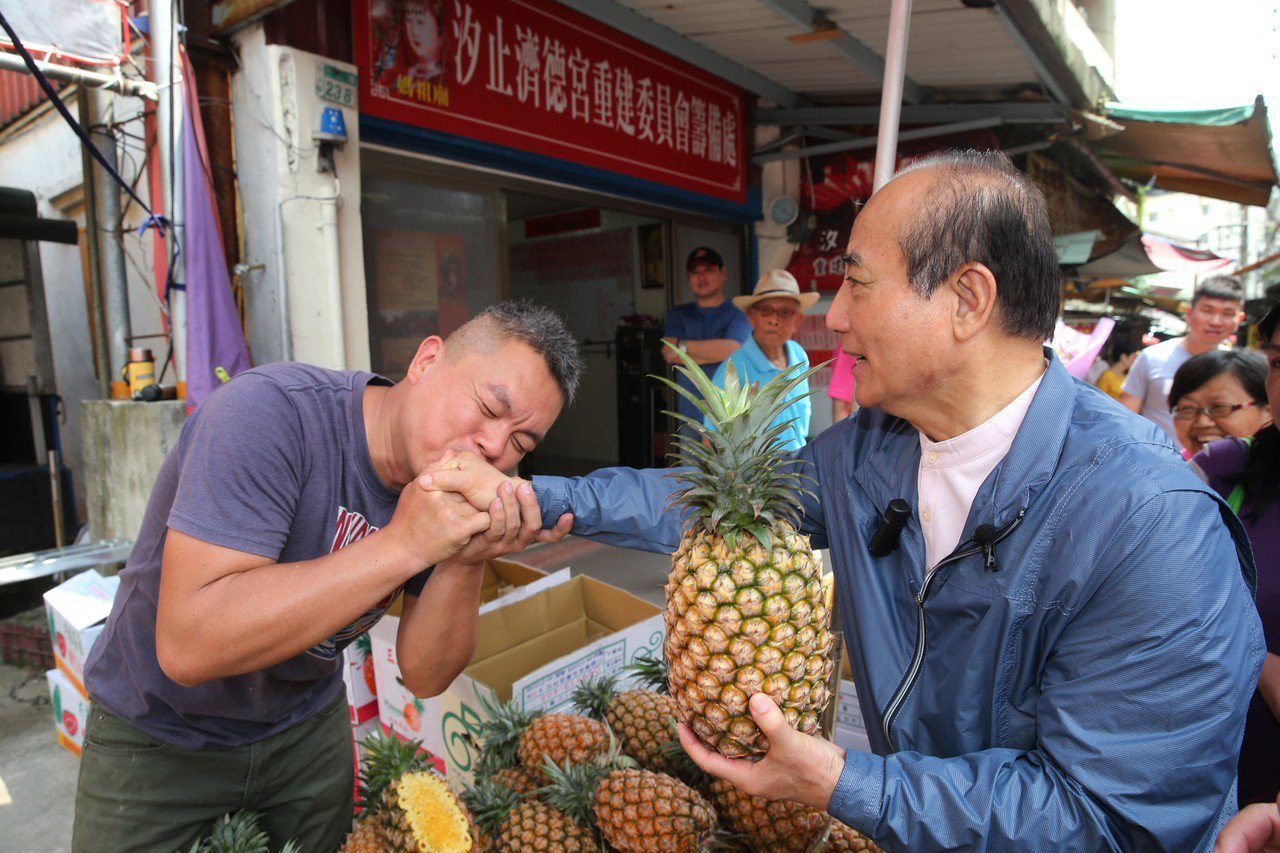 國民黨立委王金平到中正市場掃街拜票,遇到熱情的瘋狂粉絲送鳳梨、甚至親吻王的手。記...