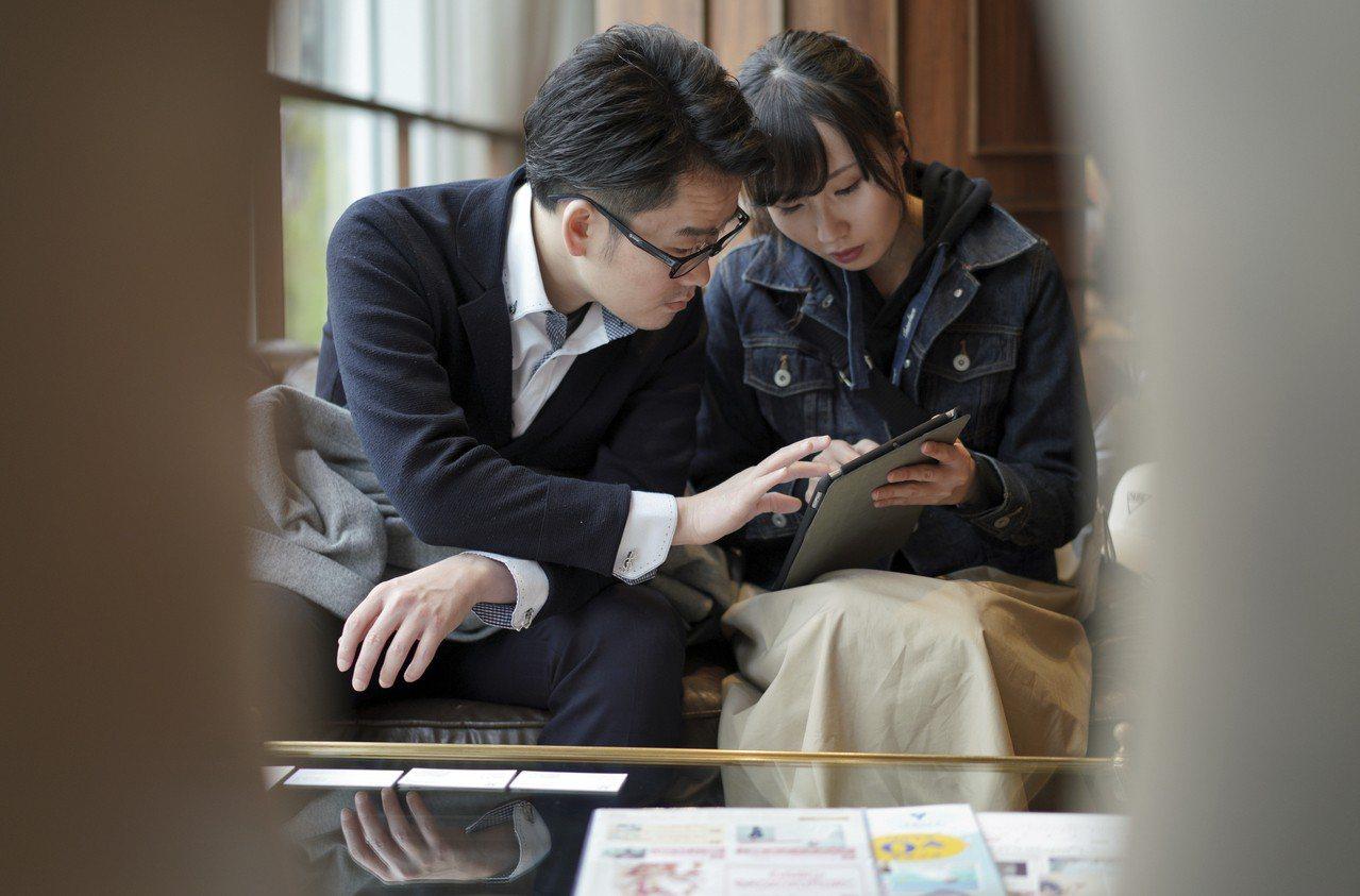 許多日本情侶打算在令和元年第一天、5月1日結婚。圖為一對情侶在東京婚紗店查看平板...