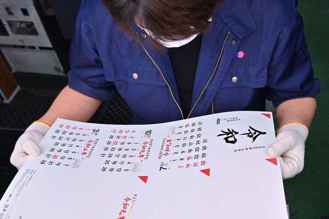 日本茨城縣月曆印刷廠員工查看印有令和年號的新版月曆。(法新社)