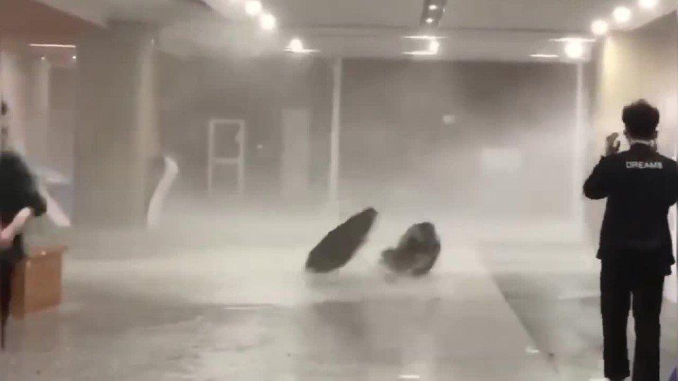 一名手拿雨傘的學生,不敵強風被直接吹倒在地。路透/Newsflare