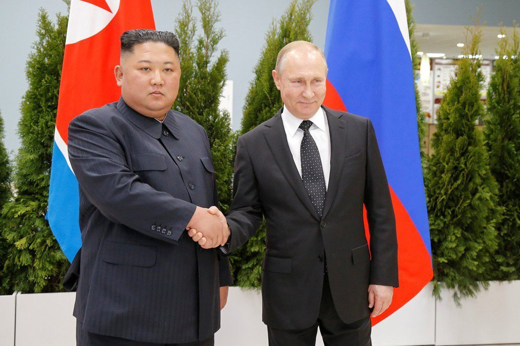 俄羅斯總統普亭(右)與北韓領導人金正恩首次舉行高峰會,兩人見面後握手。路透