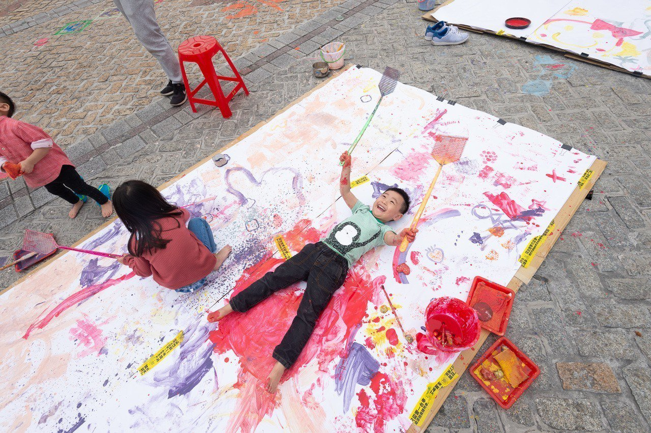 孩子躺在畫畫裡。圖/還我特色公園行動聯盟提供