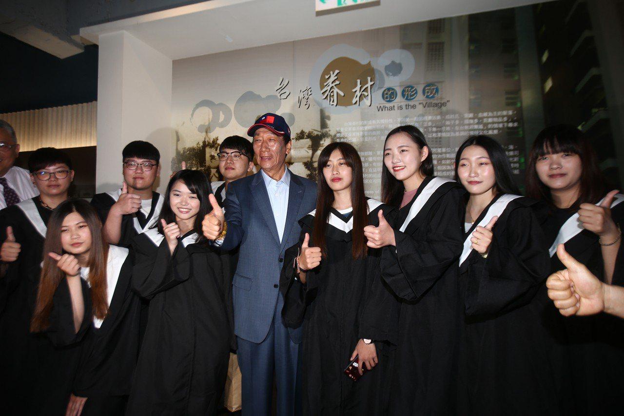 鴻海董事長郭台銘上午參觀新竹市眷村博物館,親切與前往拍畢業照的學生合影,不忘宣傳...