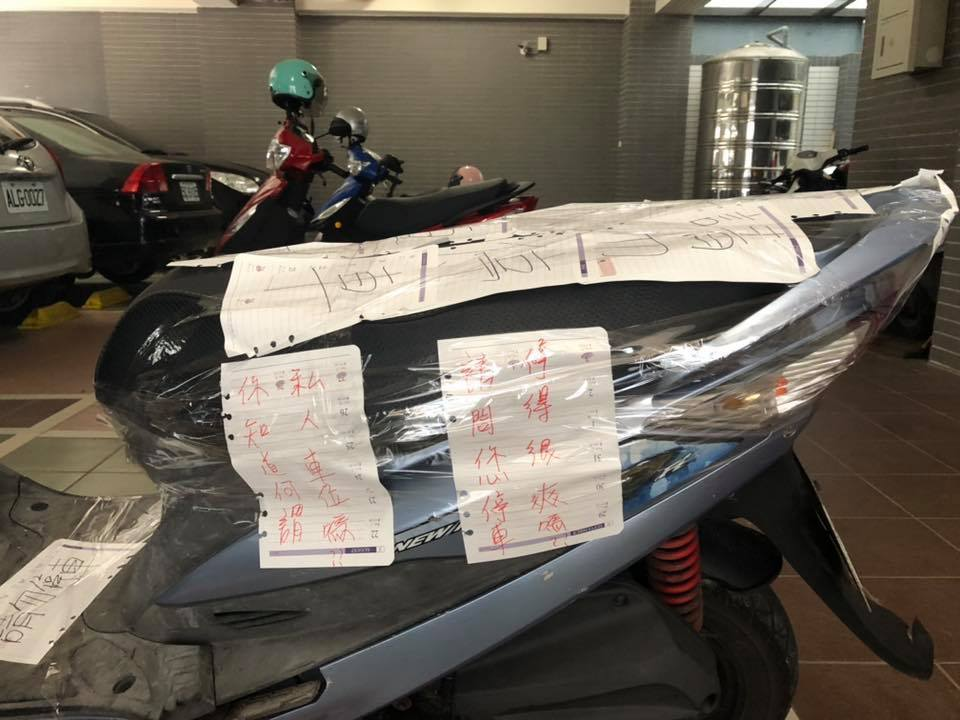 女網友在這台機車上貼上許多告示,並用膠帶綑綁。 圖/擷取自「爆怨公社」