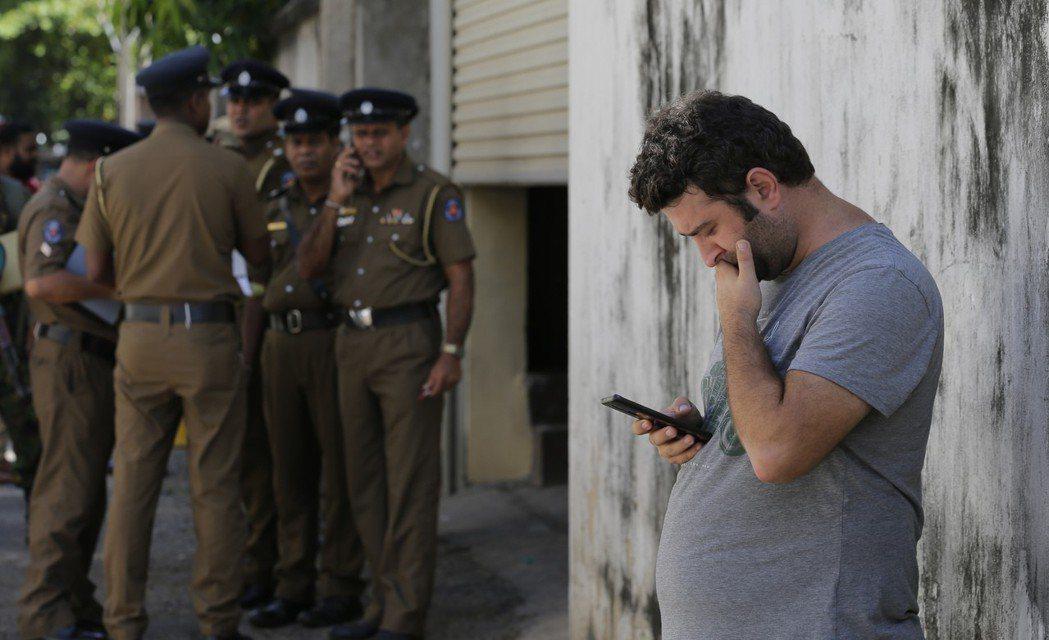 斯里蘭卡爆炸後,一名外國男子在醫院外用手機確認訊息。 圖/美聯社