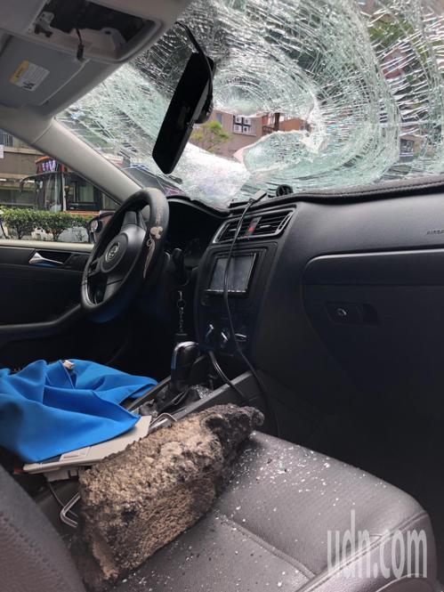 鄭姓民眾駕駛進口轎車路過停等紅燈時,車子遭爆炸噴飛落石擊中,所幸砸破擋風玻璃後落...