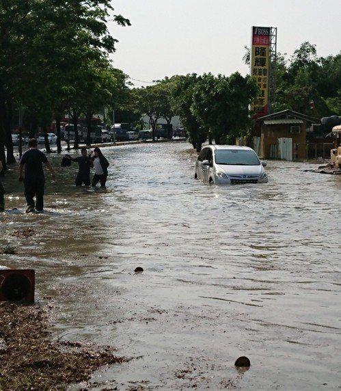 高雄市神農路因自來水管線淹水導致行經車輛受困,2名女駕駛順利脫困。記者徐白櫻/翻...