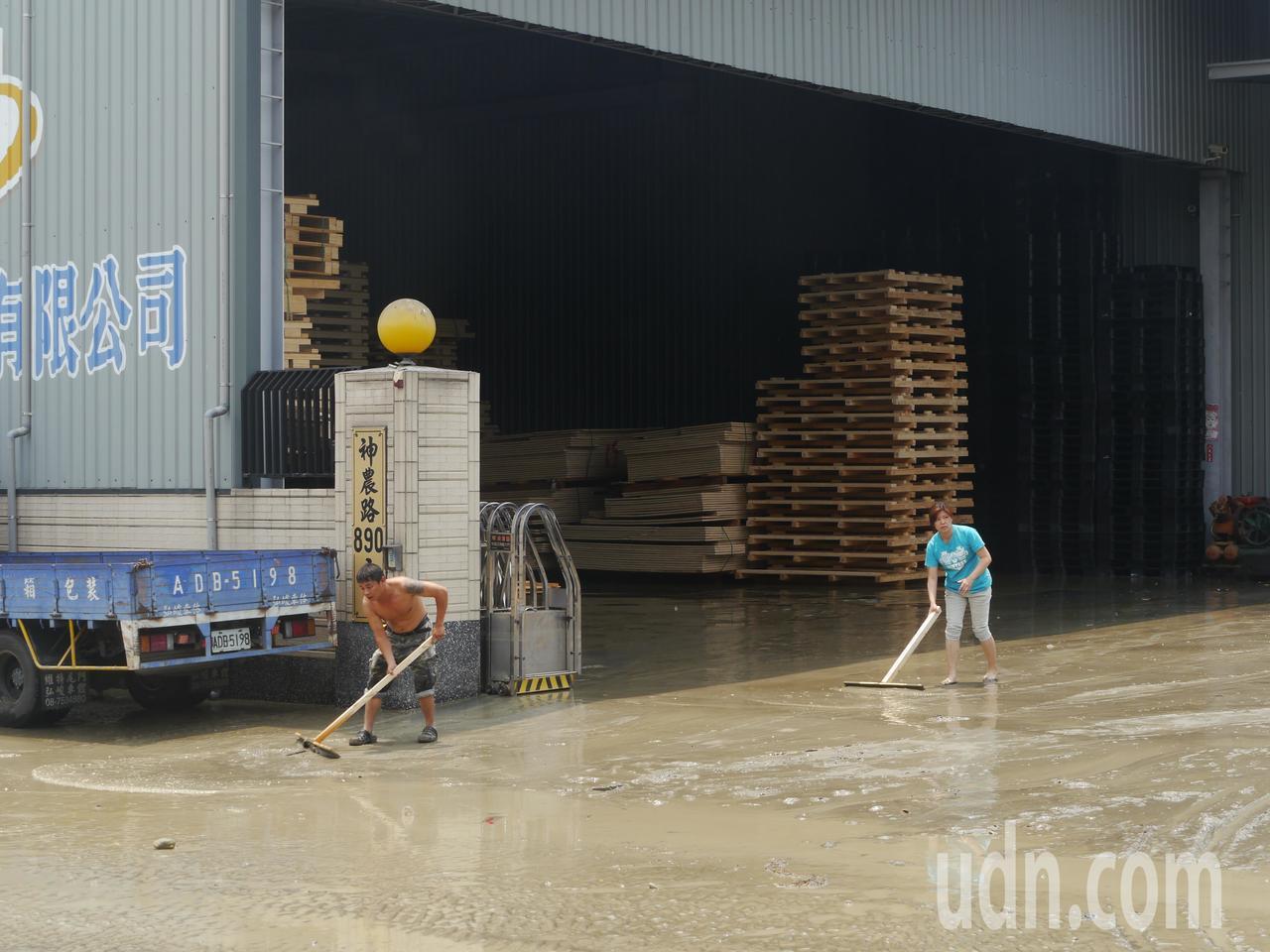 突然其來的大水淹入馬路旁木料工廠,工人忙著清理淤泥。記者徐白櫻/攝影