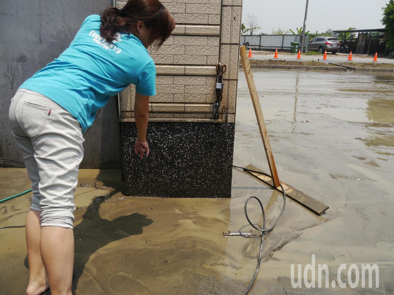 木料工廠業者說,淹水深至她手指之處,工廠損失不知要向誰求償。記者徐白櫻/攝影