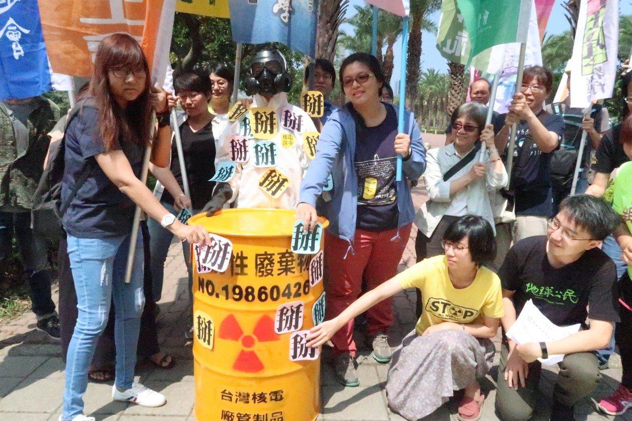 南台灣廢核行動聯盟成員將「掰」字貼上防幅射裝備人員身上及核廢料桶,象徵與只占10...