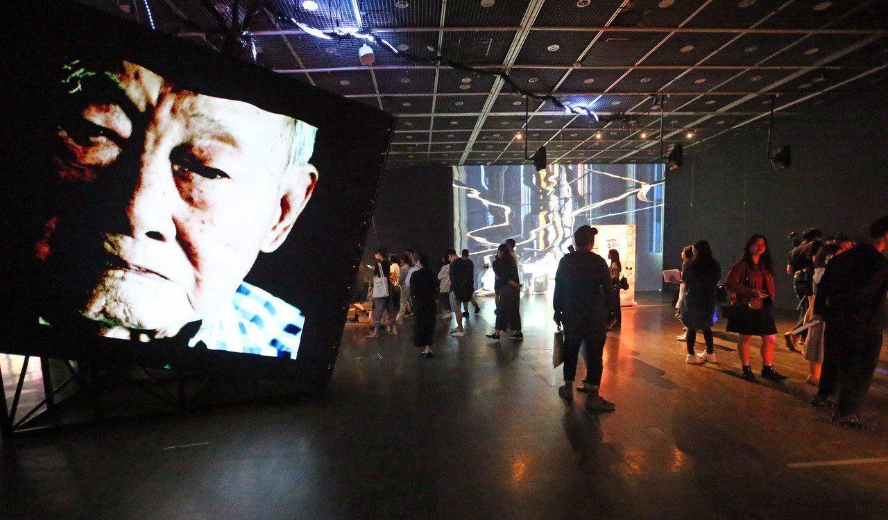 挑高大型展場中央,螢幕畫面主角是方序中的外公,透過佈滿歲月痕跡的臉龐,詮釋時間的...