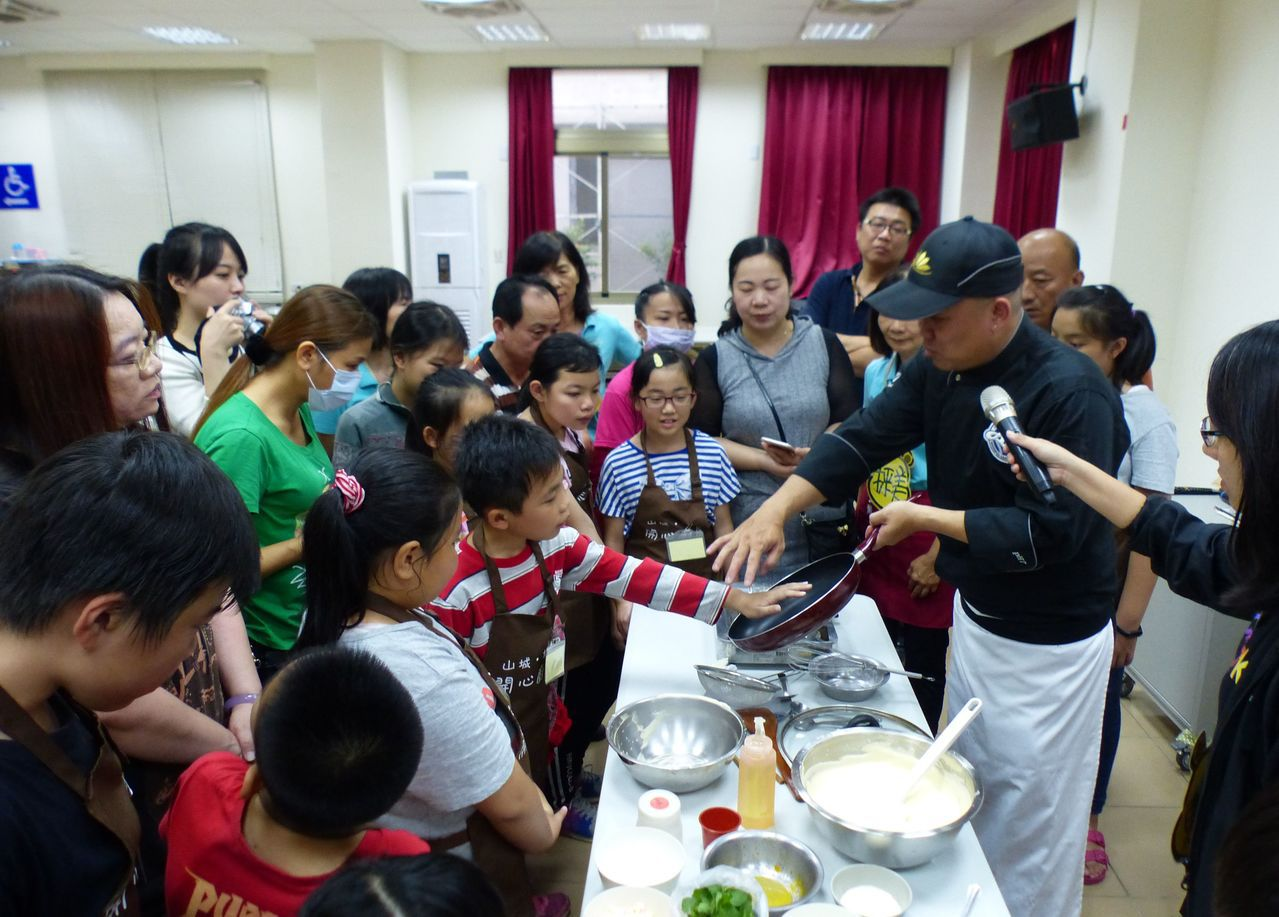 「兒童開心廚房」社團日前舉辦親子共廚,由主廚黃鴻華(右)教授製做舒芙蕾甜點技巧。...