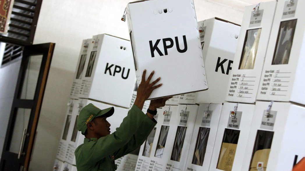 一名印尼選務人員18日在蘇門答臘島,把計算完成的一箱選票放妥。 (歐新社)