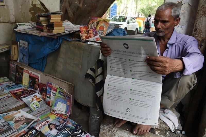 WhatsApp於去年7月在印度率先實施每個訊息最多只能轉傳5次的措施。圖為正在閱讀假消息宣導的印度民眾。 圖/法新社