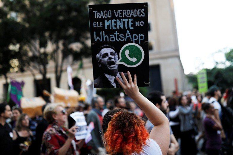 2018年10月巴西總統選舉,獲勝的波索納洛遭指控是假訊息的獲利者。圖為手持「他在WhatsApp撒謊」的民眾。 圖/路透社