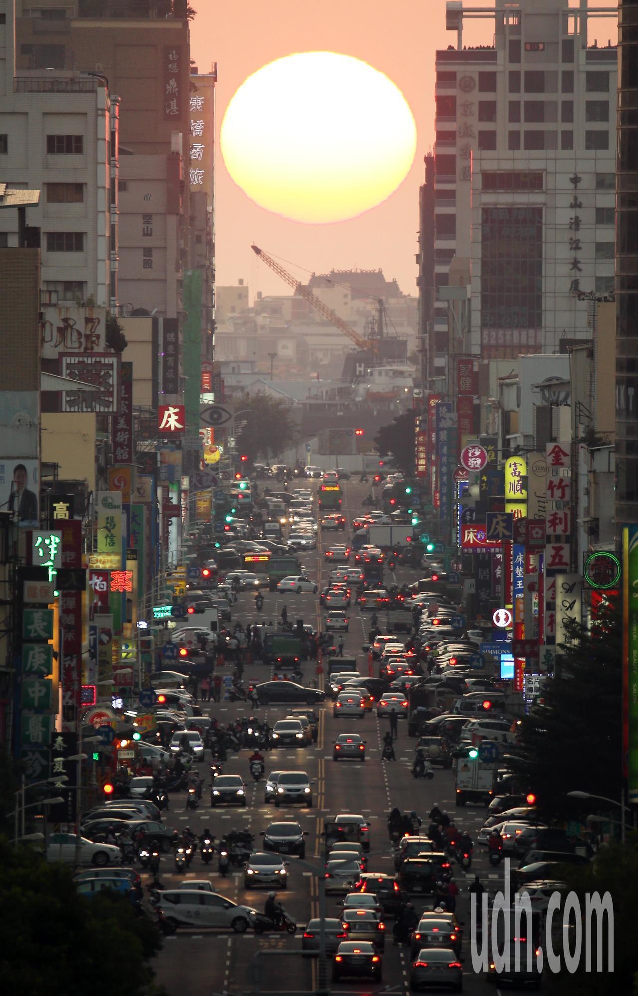 高雄青年路懸日美景今年1月底出現,火紅的夕陽緩緩地從青年路底慢慢落下,金黃陽光映...