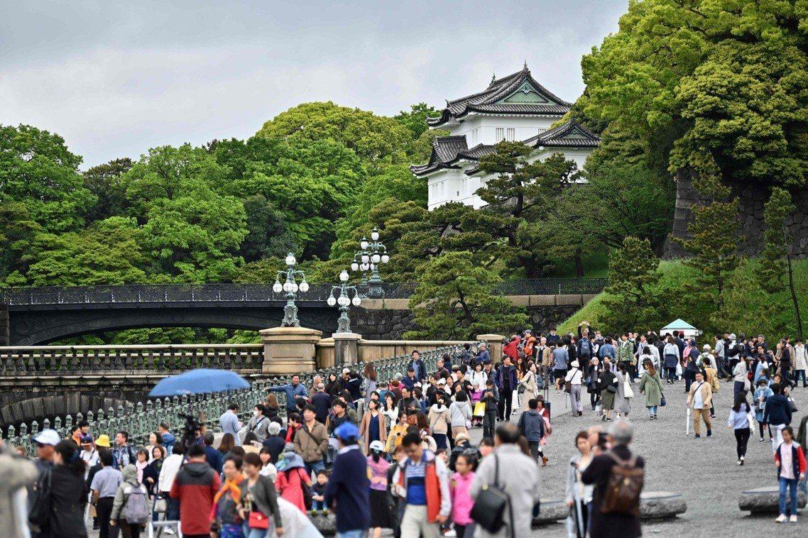 30日上午皇居外聚集的民眾,一同恭迎天皇退位之日。 圖/法新社