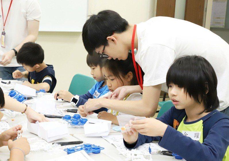 台科大資管系碩一學生胡宇謙擔任課程老師教小朋友組裝動力車。圖/台科大提供