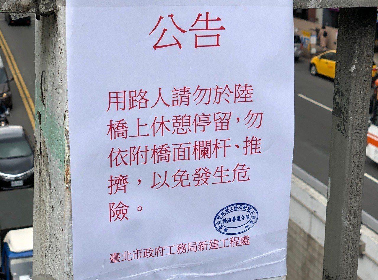 新工處人員在天橋上張貼告示,提醒民眾注意安全,不要倚靠欄杆。記者劉柏均/攝影