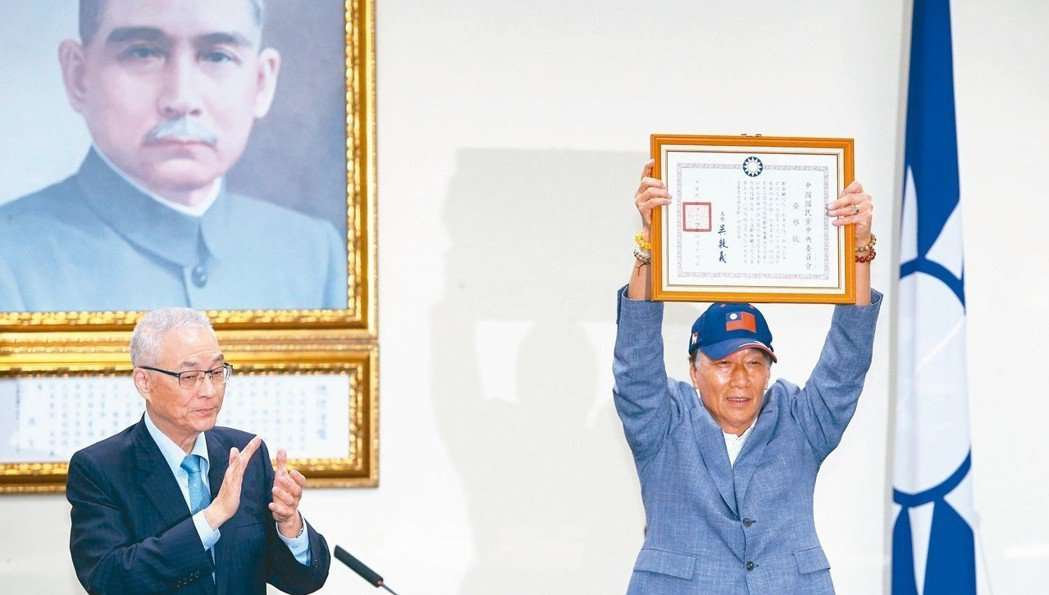 有五十年國民黨黨齡的鴻海董事長郭台銘(右)從黨主席吳敦義(左)手上接下榮譽狀,宣...