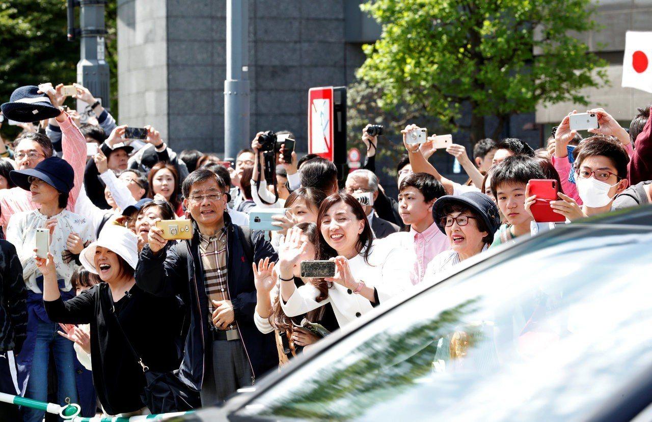 日本民眾熱情地向車隊揮手。 路透