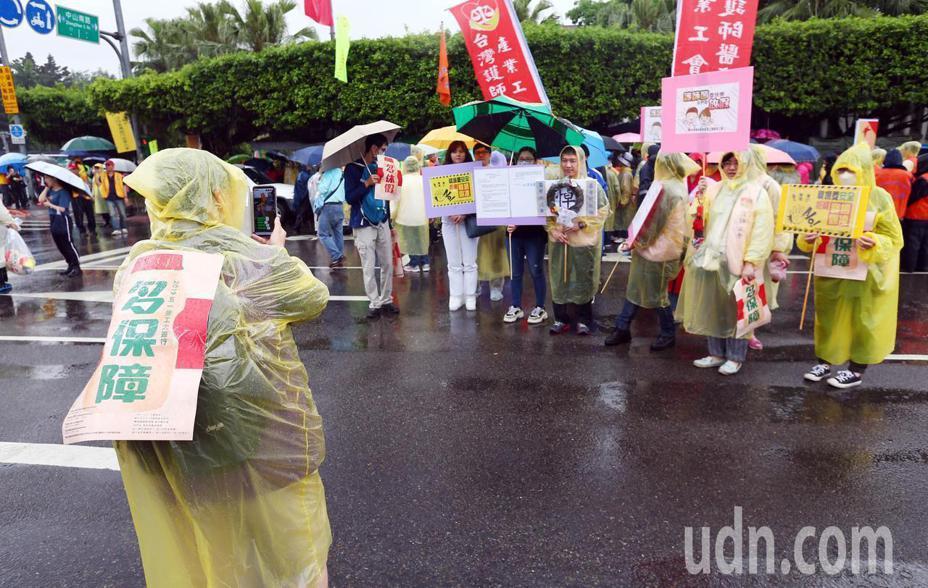 2019五一勞工大遊行下午在雨中登場,參與遊行的勞工穿著雨衣拿著標語,高喊訴求。記者杜建重/攝影