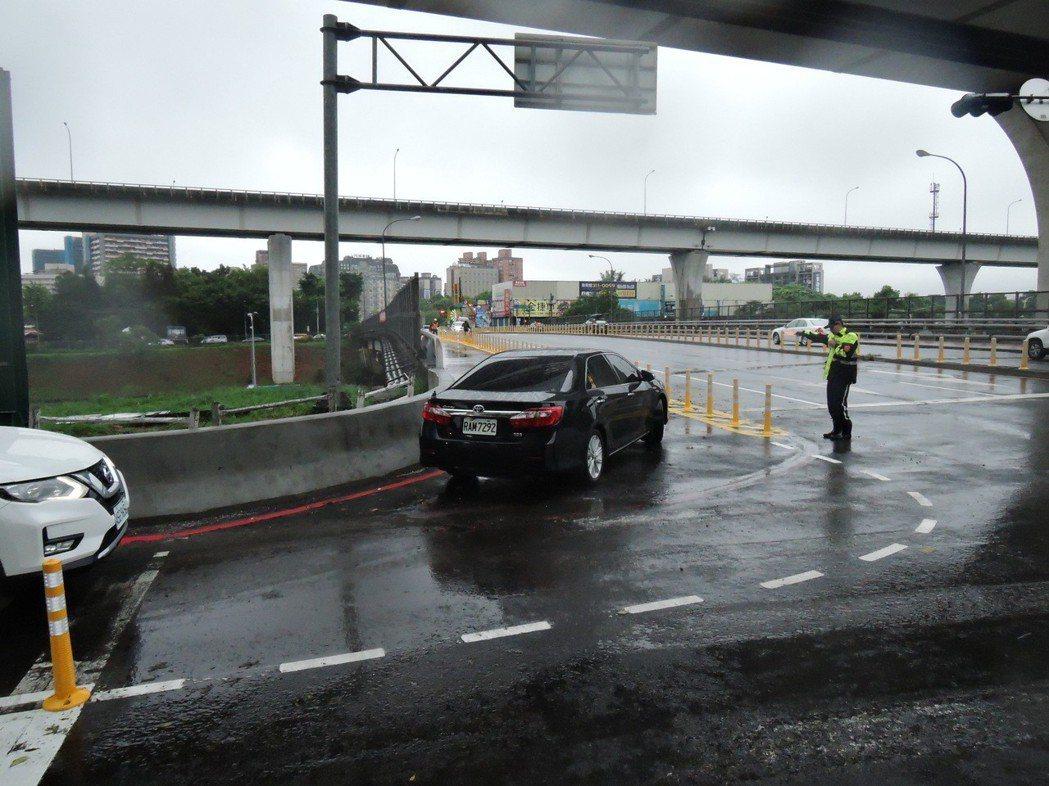 文化二路跨越橋迴轉道限行小型車,員警也到場指揮。圖/新北市交通局提供
