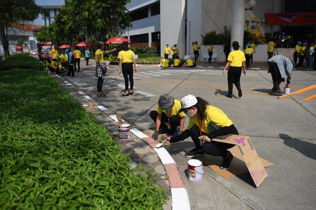 泰國郵局員工投入義工行列,為路邊標線重新上漆。(法新社)