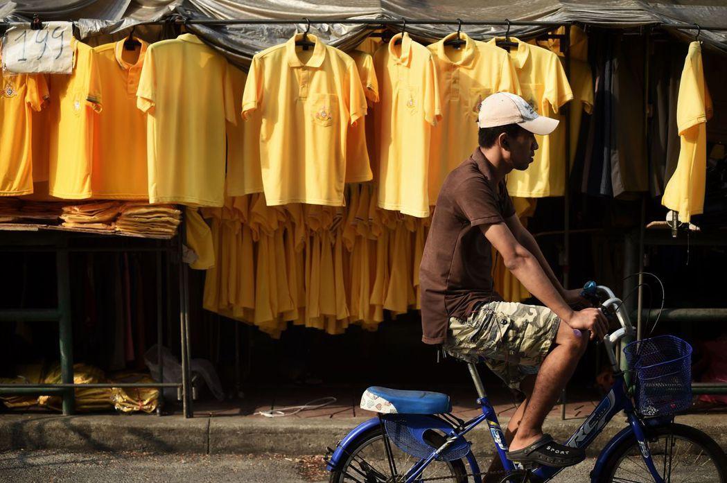 迎接泰王加冕典禮,象徵王室的黃色上衣在泰國各地熱賣。(法新社)