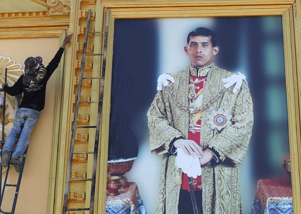 一名工人正為國防部外牆上的泰王巨幅肖像畫的邊框上色。(歐新社)