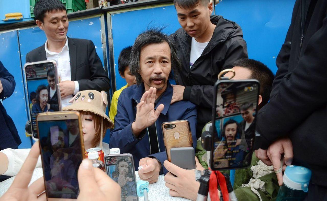 「流浪大師」沈巍(圖中)1日再度現身上海街頭。圖/取材自西安網