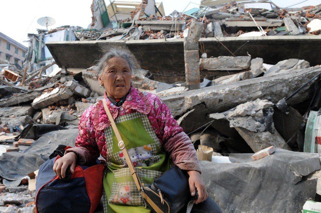 四川汶川地震給四川省多個縣市造成嚴重破壞,一位老人坐在映秀鎮一片廢墟前。圖/新華...